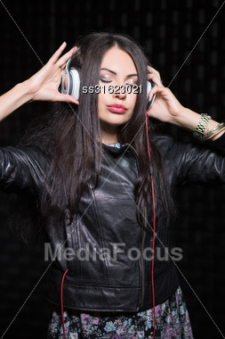 Young Brunette Posing With Headphones And Closed Eyes. Isolated On Black Stock Photo