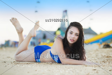 Young Brunette Posing On The Sand Near Recreation Park Stock Photo