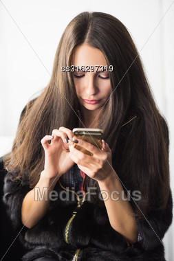 Young Brunette Wearing Fur Coat Posing With A Phone Stock Photo