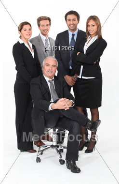 Young Business Team Standing Behind Their Boss Stock Photo