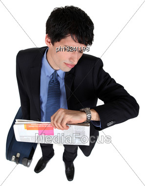 Young Businessman Looking At His Watch, Studio Shot Stock Photo
