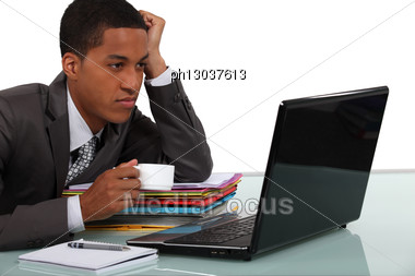 Young Businessman Taking A Break In Front Of His Laptop Stock Photo