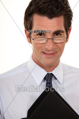 Young Businessman Wearing Glasses And Holding Folder Stock Photo