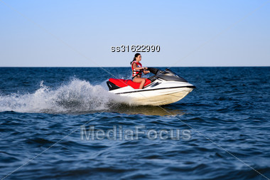 Young Caucasian Woman In Life Jacket On A Wave Runner Stock Photo