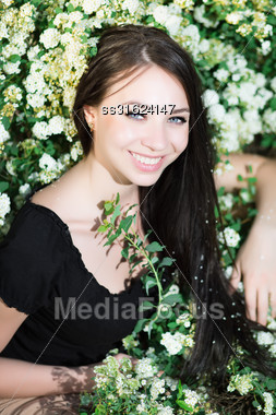 Young Cheerful Brunette Posing In The Flowering Bushes Stock Photo