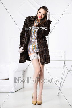 Young Cheerful Brunette Posing In Short Dress And Fur Coat Stock Photo