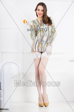 Young Cheerful Brunette Wearing Frank Dress Holding A Tangerine Stock Photo