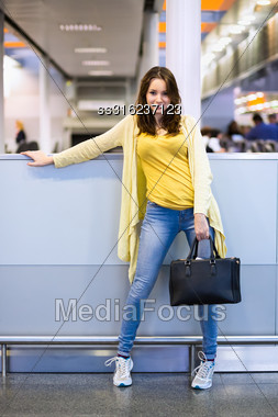 Young Cheerful Woman Posing In The Airport Terminal Stock Photo