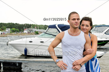 Young Couple Against Pier With Boats. Stock Photo