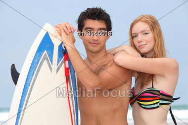 Young Couple At The Beach With Surfboard Stock Photo