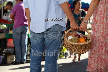 Young Couple At Market Buying Fruits Stock Photo