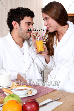 Young Couple In Bathrobe Drinking Orange Juice Out Of Straw Stock Photo
