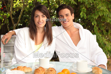 Young Couple Having Breakfast Outside Stock Photo