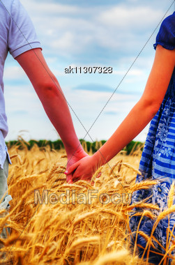 Young Couple Holding Hands In The Evening Stock Photo