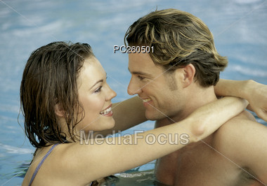 Young Couple Hugging in Water Stock Photo