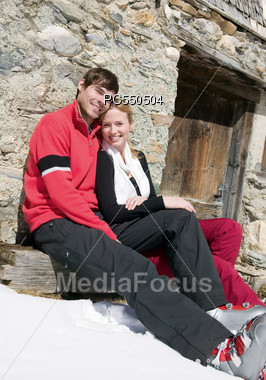 Young Couple Outside Cabin In The Snow Stock Photo