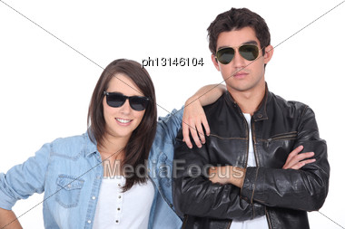 Young Couple Posing In Sunglasses And Leather Jacket Stock Photo