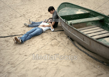 Young Couple Resting On The Beach Leaning Against Boat Stock Photo