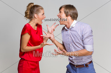 Young Couple Screaming At Each Other Over Grey Background Stock Photo