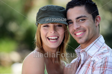 Young Couple Stood In The Park Stock Photo