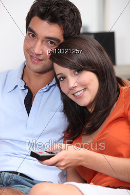 Young Couple Watching TV With A Remote Control Stock Photo