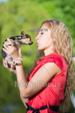 Young Curly Blond Woman Kissing Little Dog Stock Photo