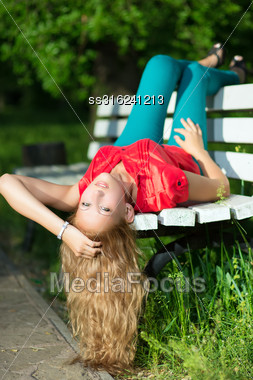 Young Curly Blond Woman Lying On The Bench Stock Photo