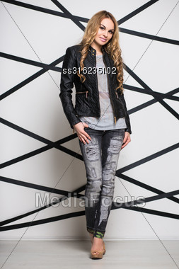 Young Curly Blond Woman Wearing Black Jacket And Jeans Stock Photo