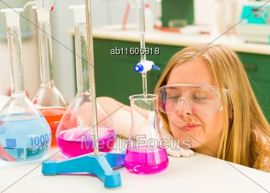 Young Cute Student With Protective Glasses Titrating With Acid At The Laboratory Stock Photo