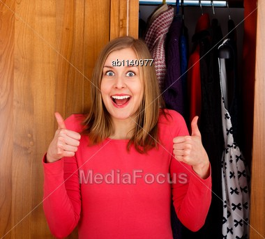 Young Excited Woman Showing Thumbs Up For Her Closet Stock Photo