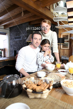 Young Family Gathered In The Kitchen Stock Photo