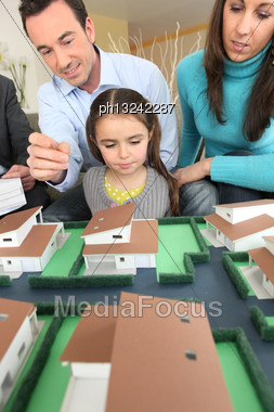 Young Family Looking At Model Housing Stock Photo