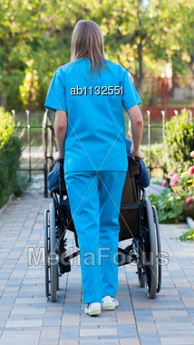Young Female Doctor Pushing An Old Patient In Wheelchair Stock Photo