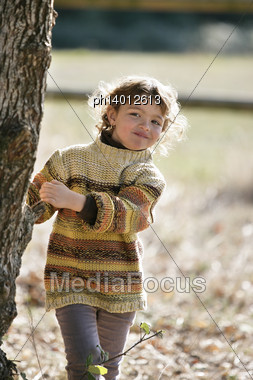 Young Girl Playing Amongst The Trees Stock Photo