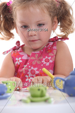 Young Girl Playing With Her Tea Set Stock Photo