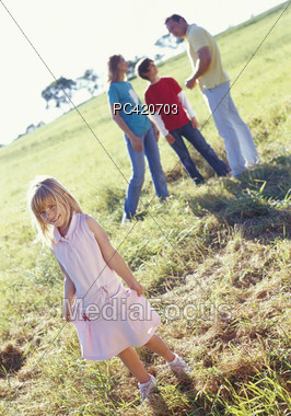 Young Girl Standing In Fields, Family In Background Stock Photo