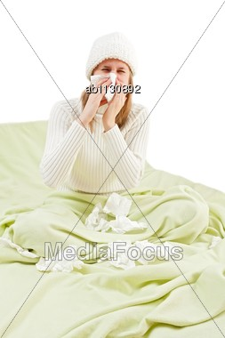 Young Girl Suffering From Influenza, Staying In Bed And Blowing Her Nose Stock Photo