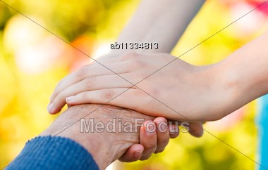 Young Hand Holding An Elderly Man's Hand - Conceptual Picture Stock Photo