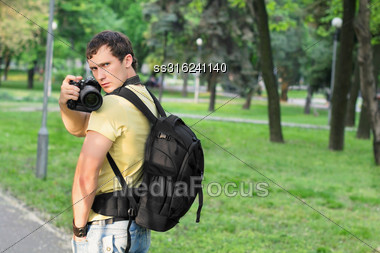 Young Handsome Man With Serious Look Making Photos In The Park Stock Photo