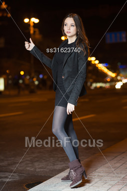 Young Hitch-hiking Brunette Wearing Black Dress And Jacket Stock Photo