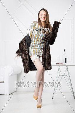 Young Laughing Brunette Posing In Short Dress And Fur Coat Stock Photo