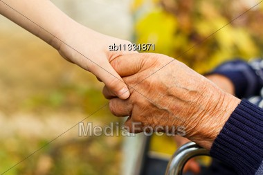 Young Little Boy Shaking Hands With Old Man Stock Photo