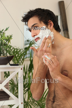 Young Man Applying Shaving Cream Stock Photo