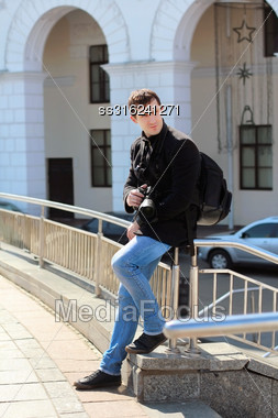 Young Man In Black Coat And Blue Jeans Posing With Camera Outdoors Stock Photo