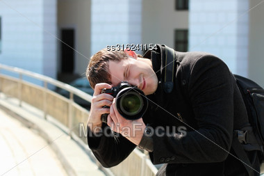 Young Man In Black Coat With Professional Camera Taking Photograph Outdoors Stock Photo