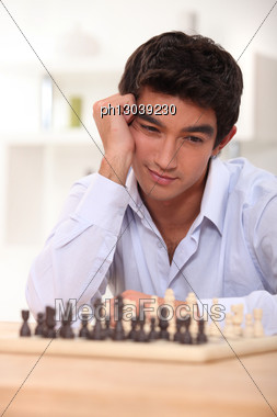 Young Man Contemplating His Next Chess Move Stock Photo