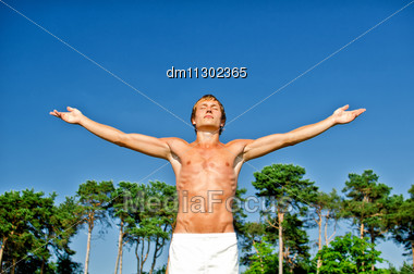 Young Man Doing Meditation Exercises On Sky Background Stock Photo