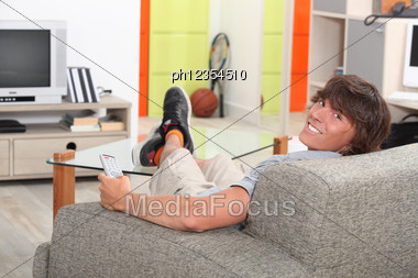 Young Man With His Feet On The Table Stock Photo