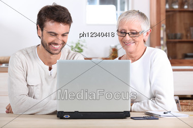 Young Man And His Mother Using Laptop Stock Photo
