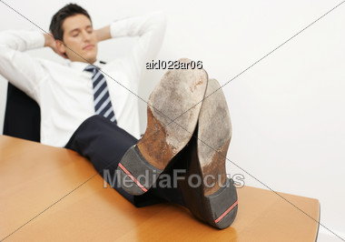 Young Man Leaning Back At His Desk Relaxing Stock Photo